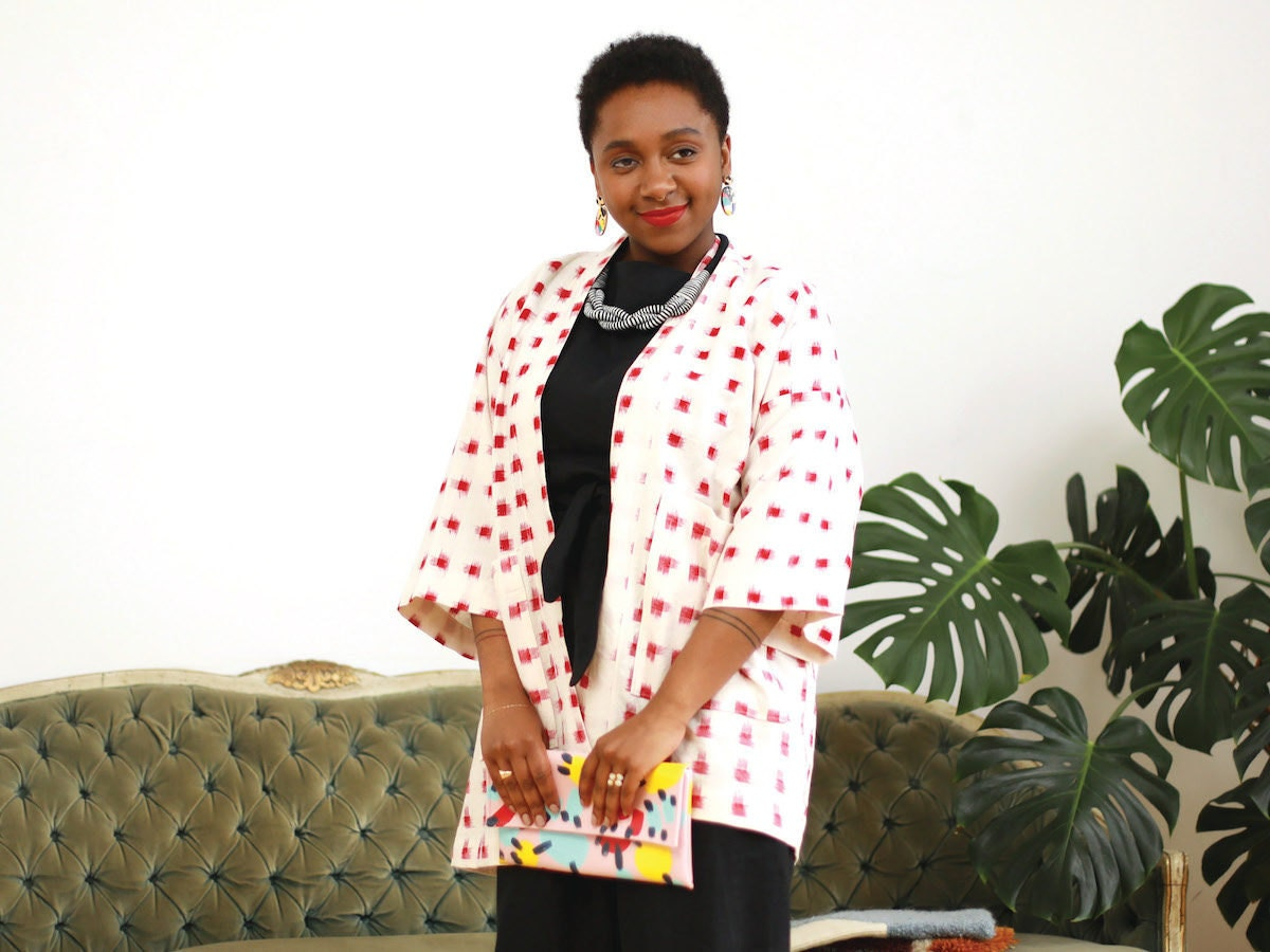 Model wearing a black linen jumpsuit, printed kimono, and colorful accessories