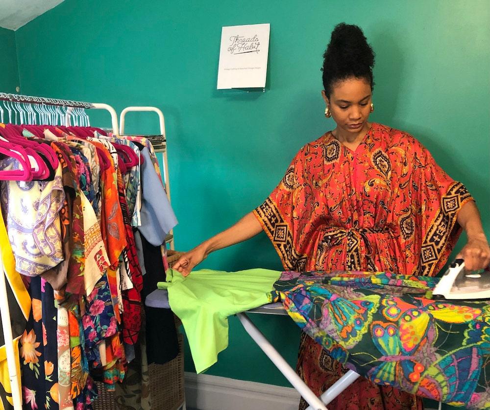 Halima ironing a vintage dress.