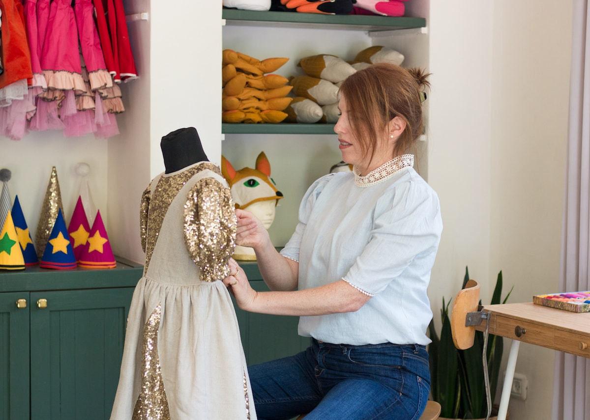 Inbal working on her golden queen costume in her studio