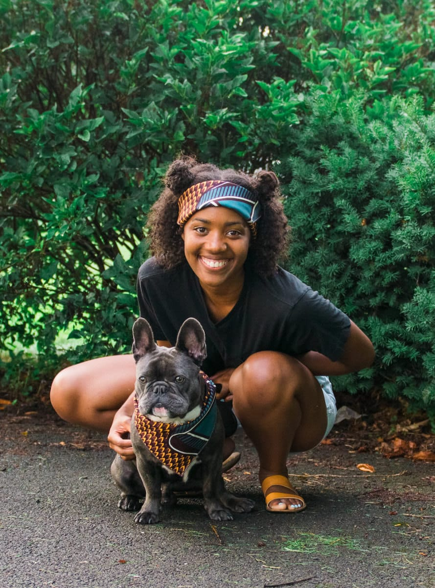 A woman and her French bulldog model a matching head wrap and bandana.