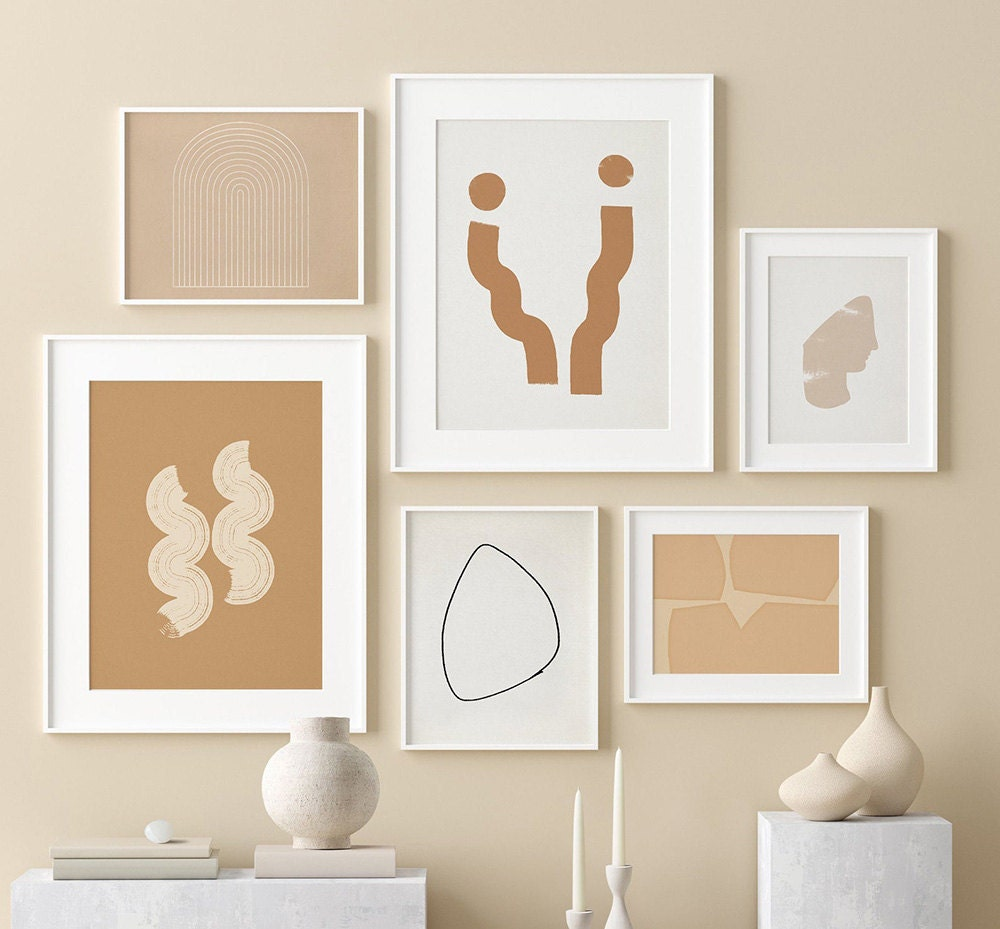 A gallery wall with abstract designs in warm colors.