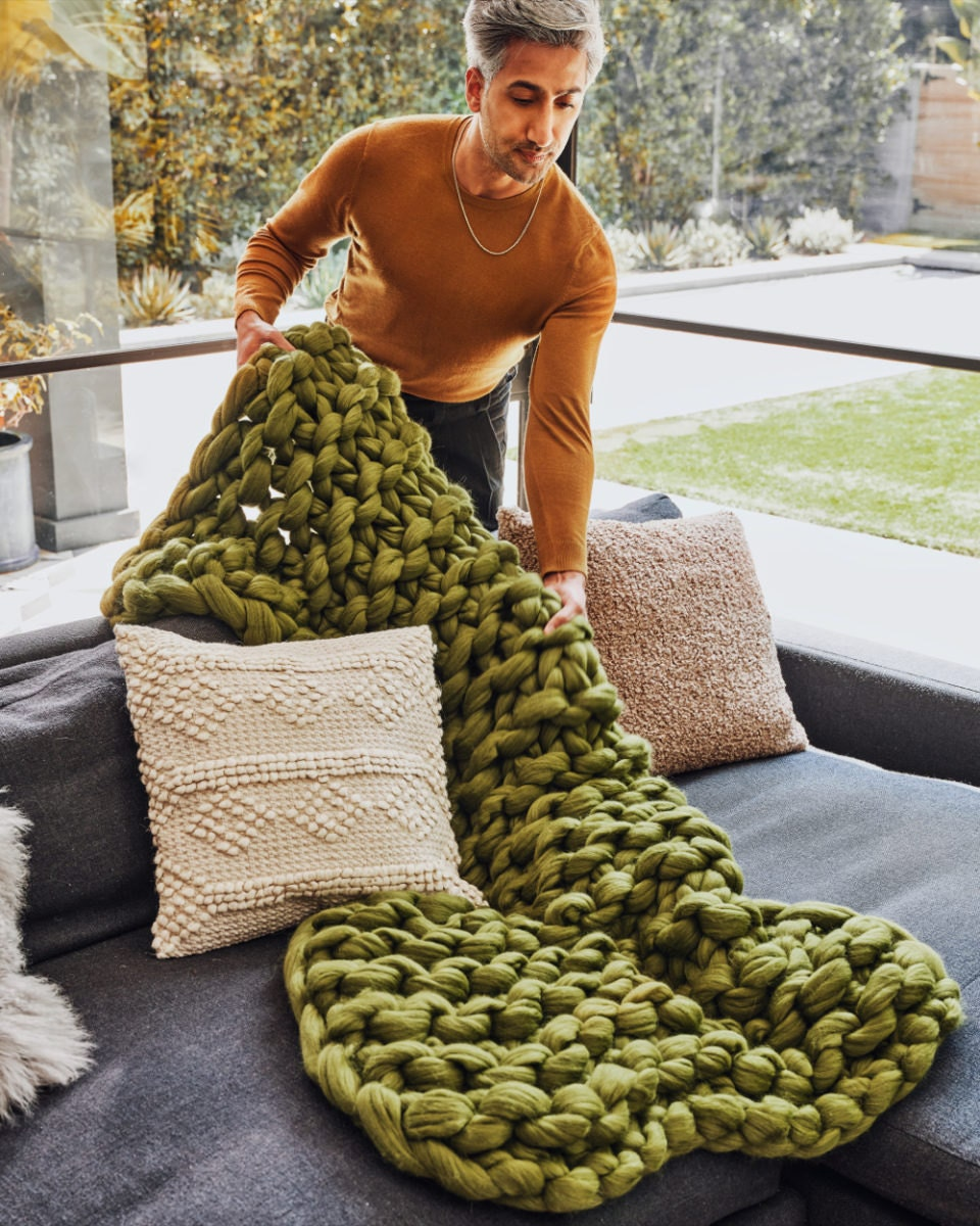 Tan lays an olive green chunky knit throw blanket from the Tan France x Etsy collection on a couch