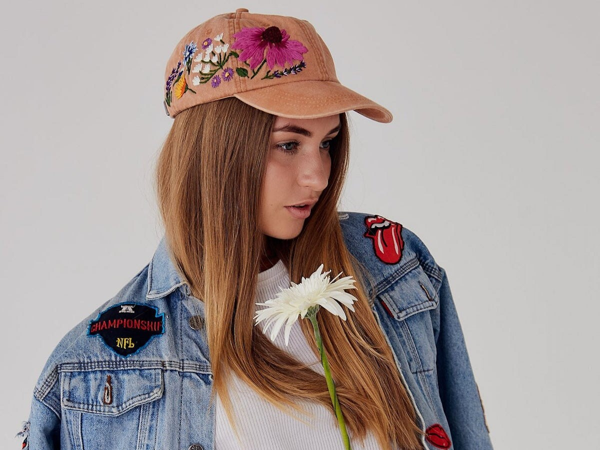 A girl modeling an embroidered baseball cap and denim jacket