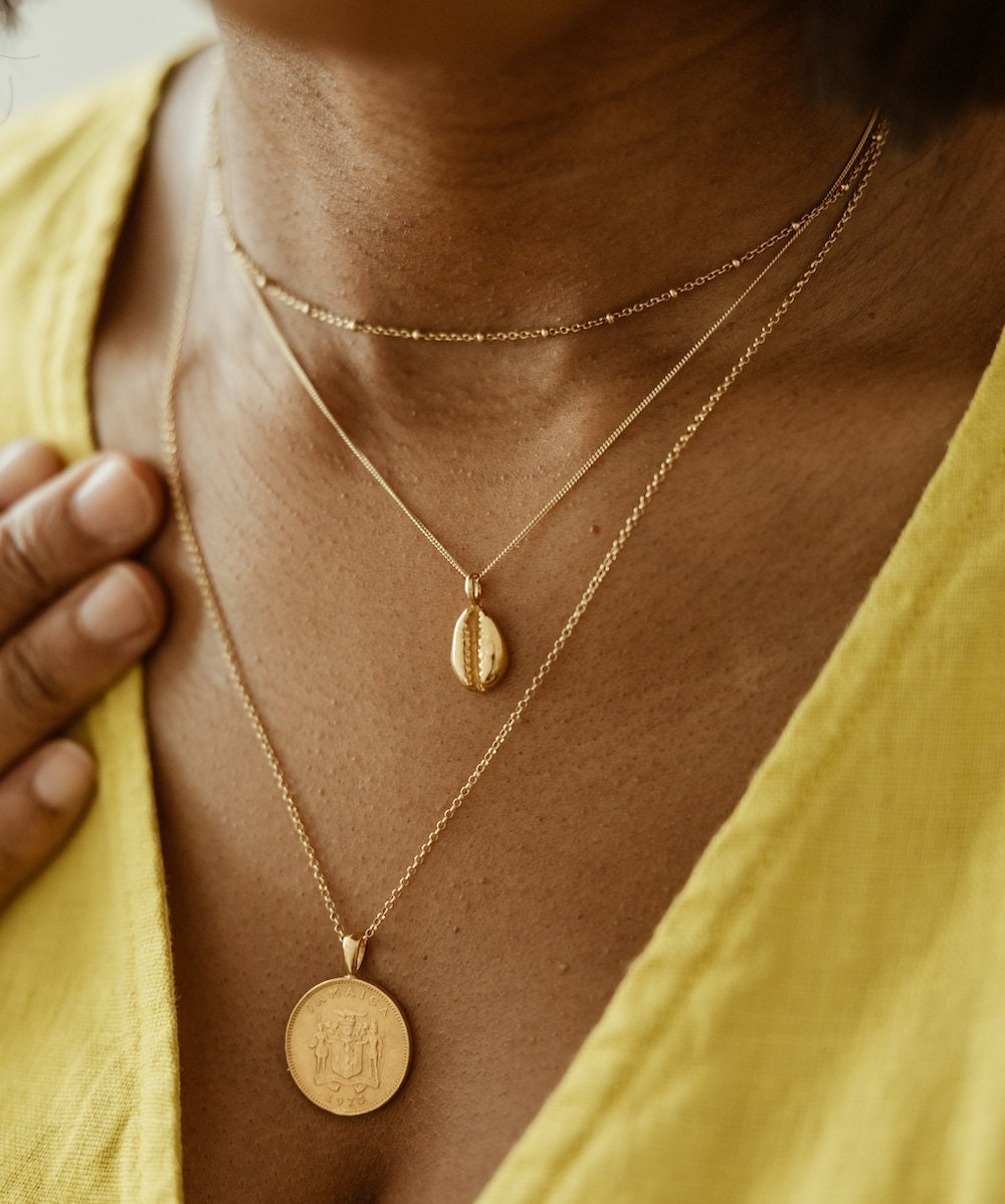 Gold Jamaican coin necklace and coffee bean necklace both from Omi Woods