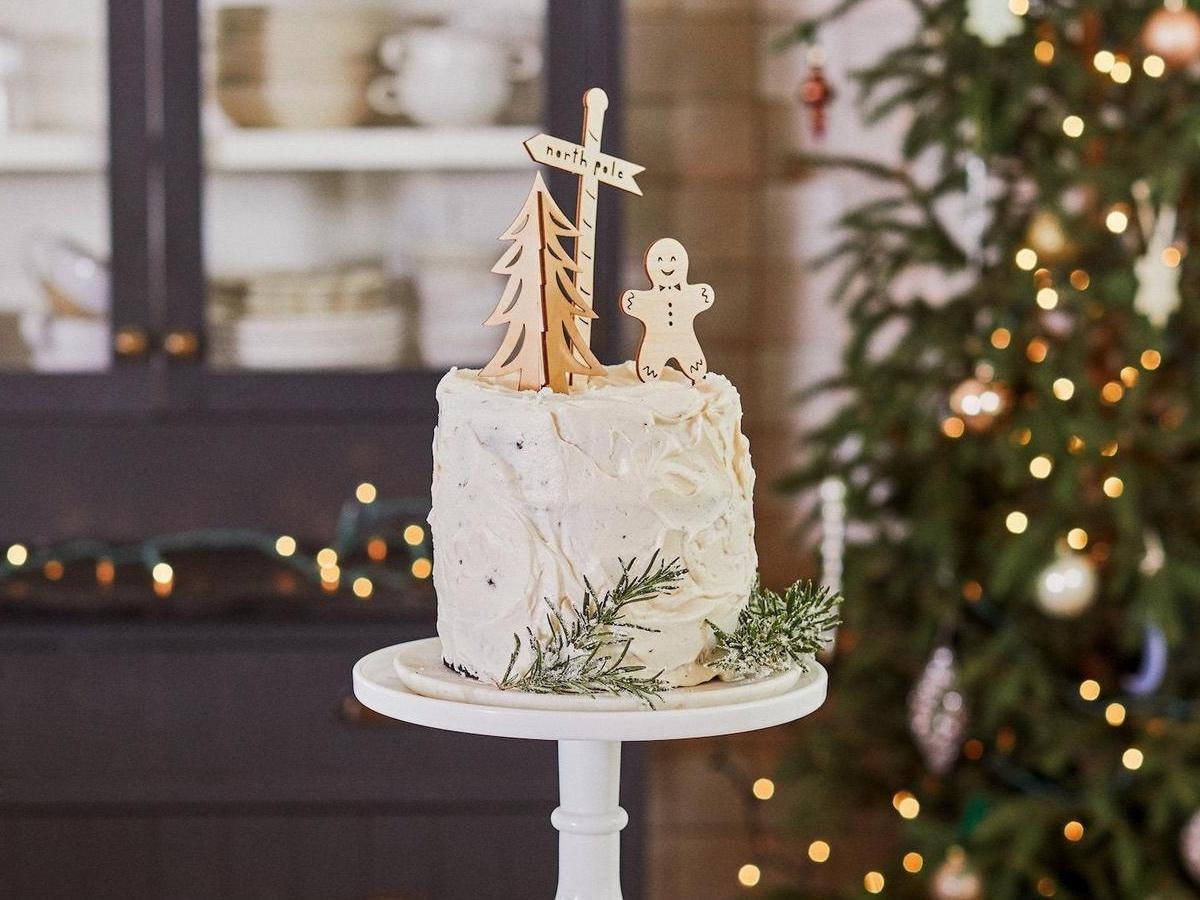 Holiday cake toppers by Light + Paper (from the Half Baked Harvest x Etsy collection) styled on a frosted cake.