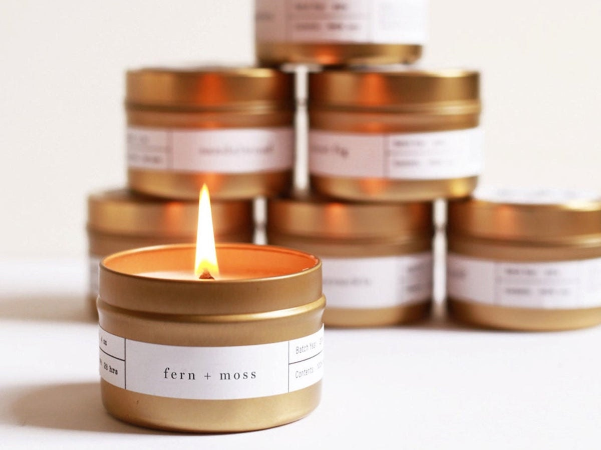 A stack of brushed gold travel candles from Brooklyn Candle Studio