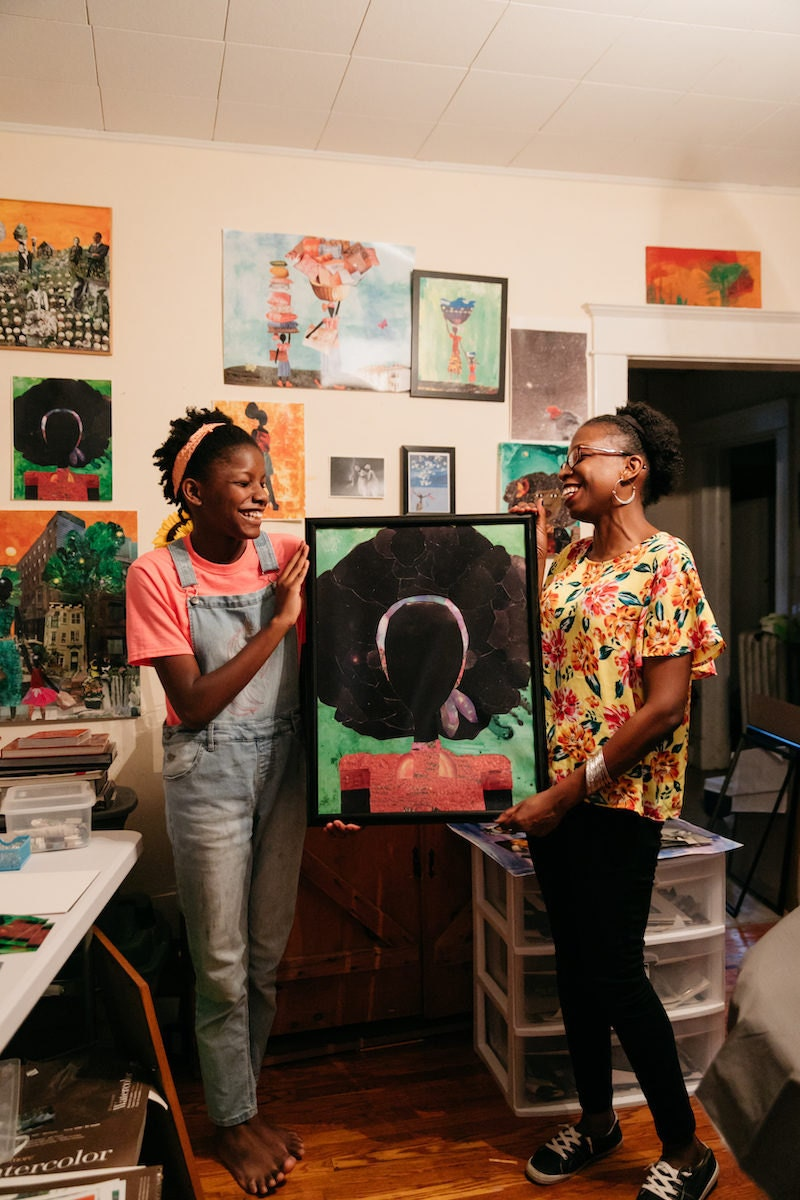 """Mirlande and her daughter hold a framed print of """"Girl with the Big Afro"""""""