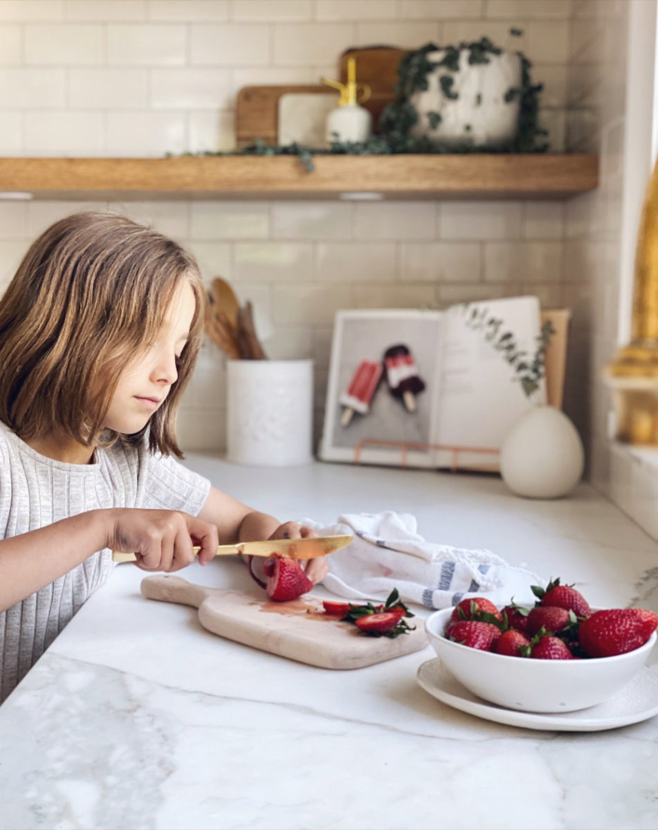 One of Kristine's daughters slices strawberries on a maple wood cutting board.