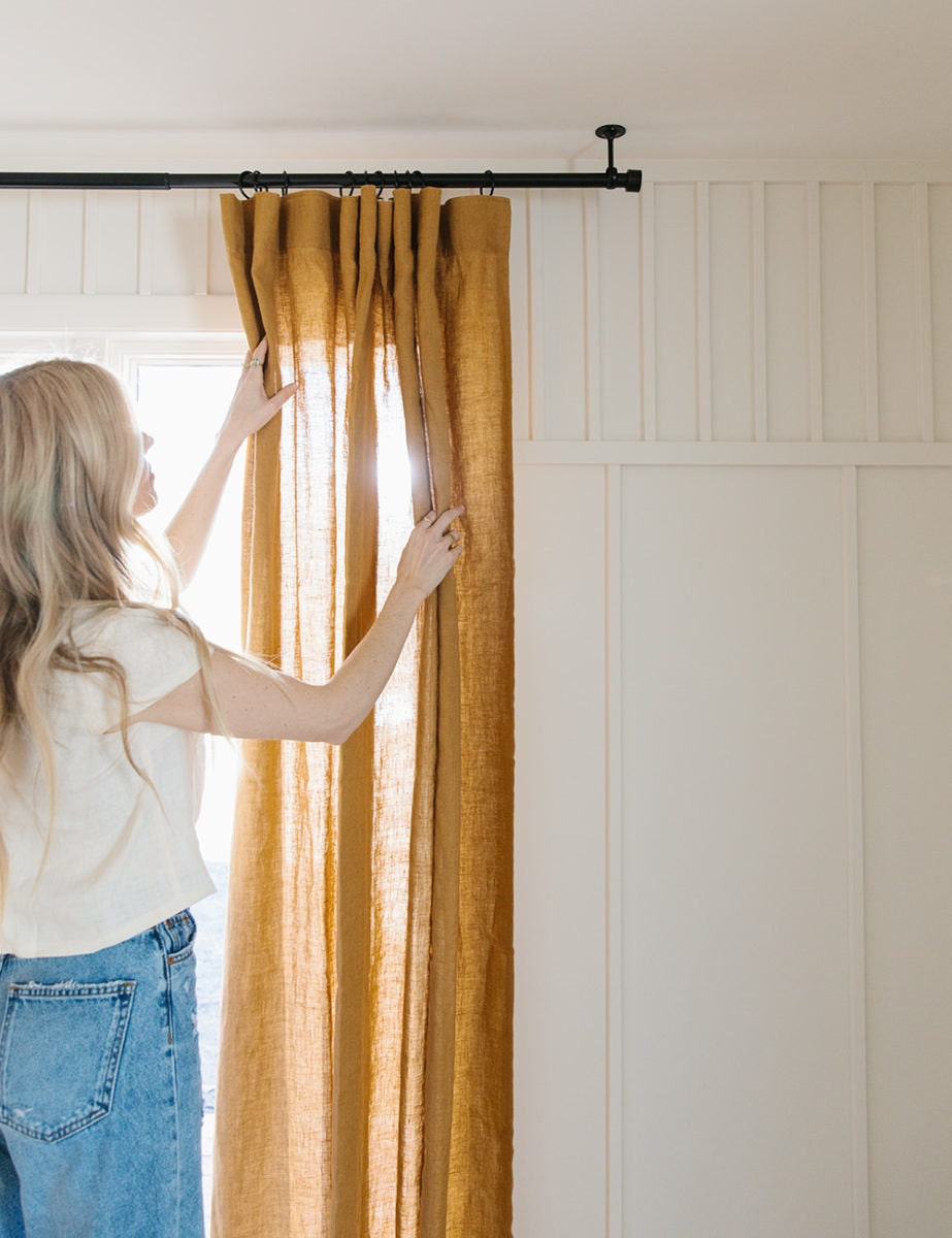 Sarah opens the amber-colored linen drapes while sunshine beams through them.