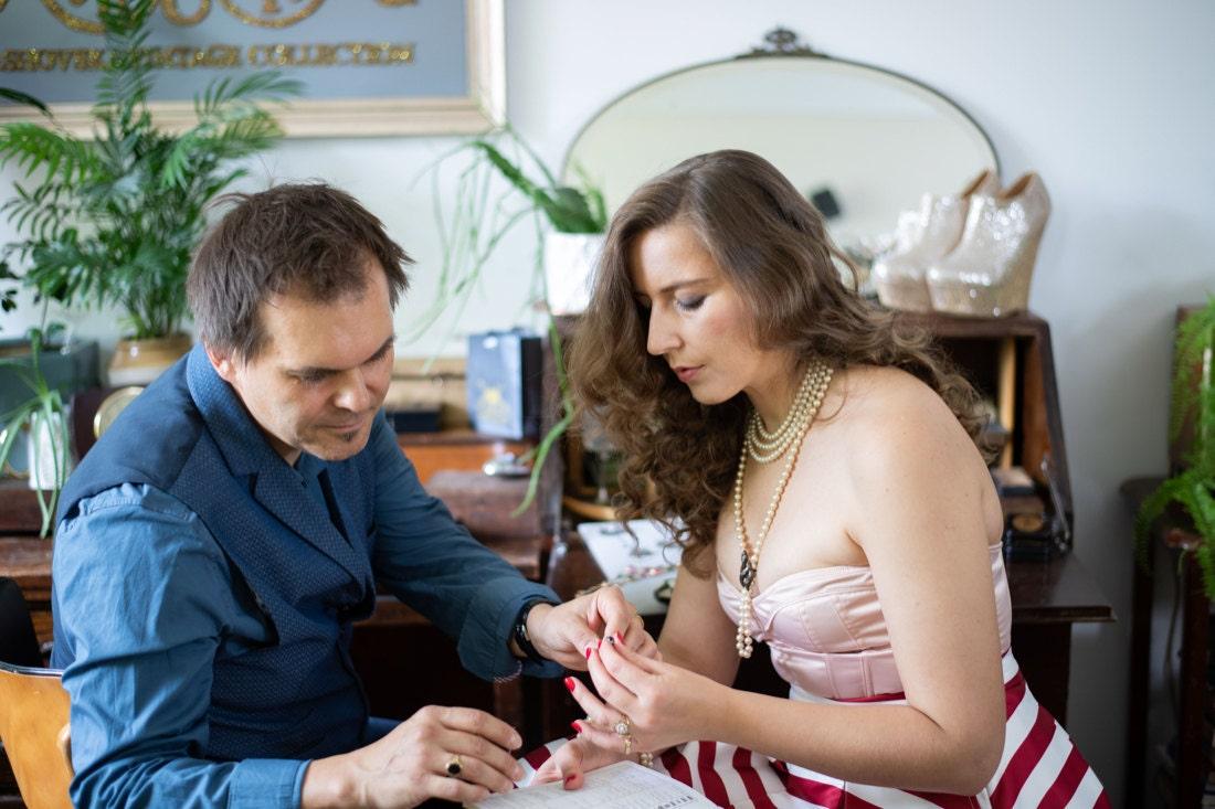 KK and Sebastian examine a vintage gemstone together