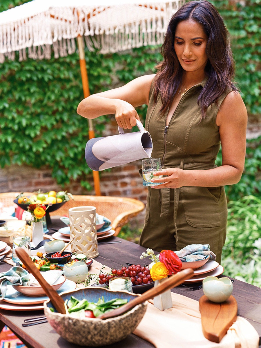 Padma Lakshmi pours a glass of water from a rustic grey pitcher