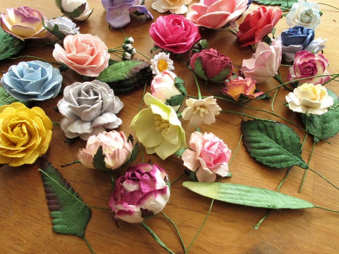 Multi-colored paper florals laid out on Orawee's tabletop