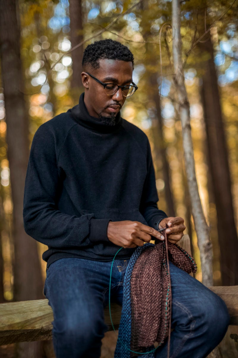 Designer Nathan Bryant knits a new piece out of blue and purple yarn