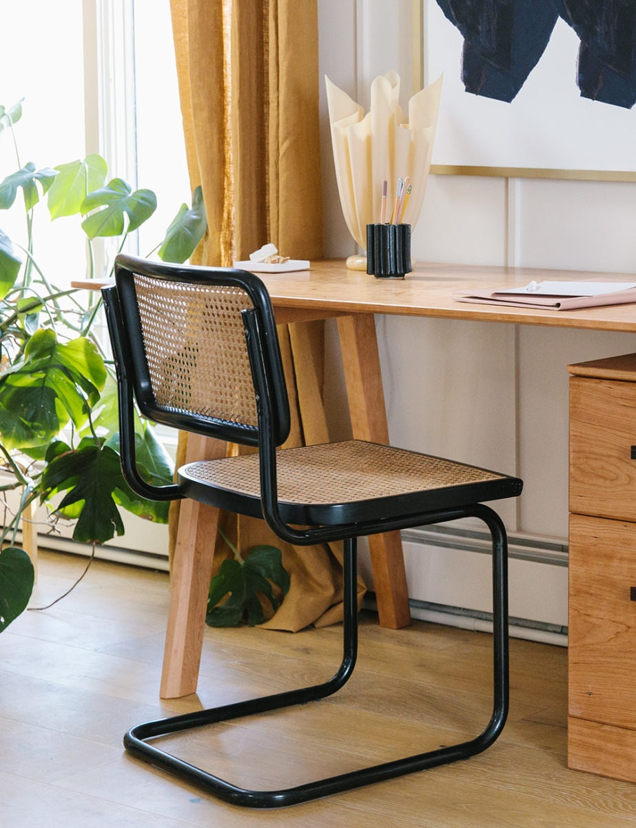 A black rattan Cesca chair sits in front of a wooden desk. Nearby is a leafy green Monstera plant.