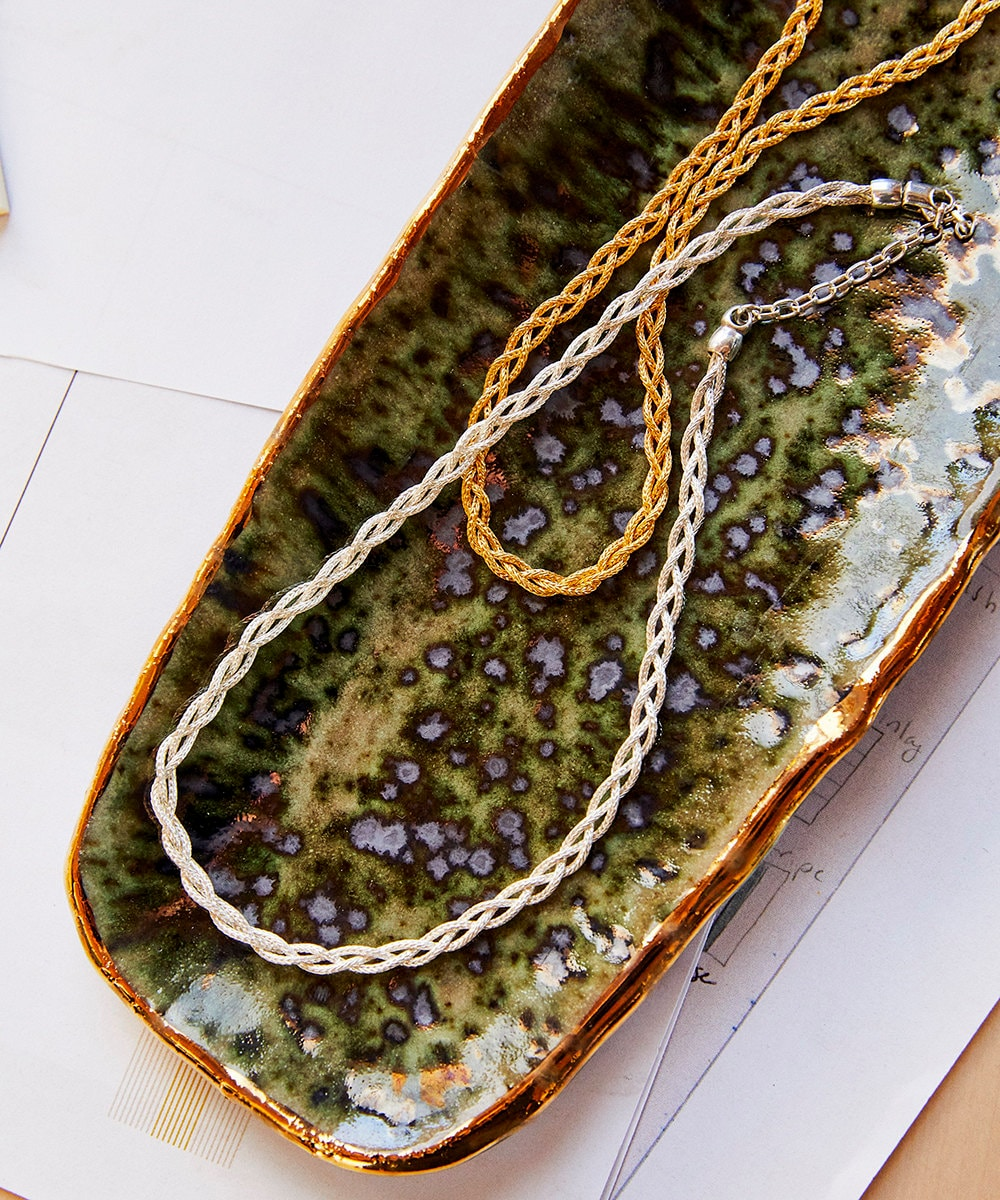 A gold chain and a silver chain in a green dish.