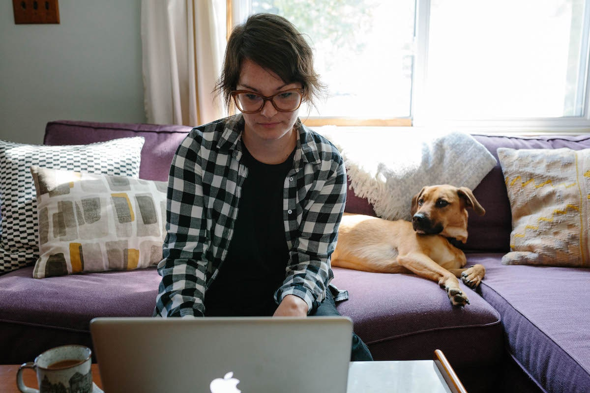 Brenda sitting on her couch with her dog, working on her computer