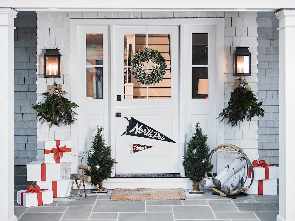 A front door styled with rustic decor for the holidays.
