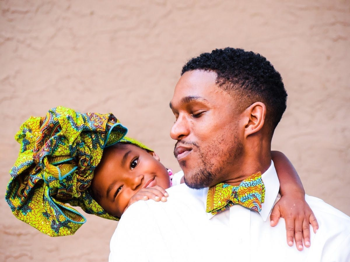 Father and daughter wearing matching African wax print bow tie and headwrap