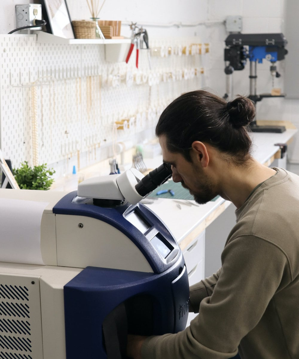 Abe uses the laser engraving machine to customize a piece.