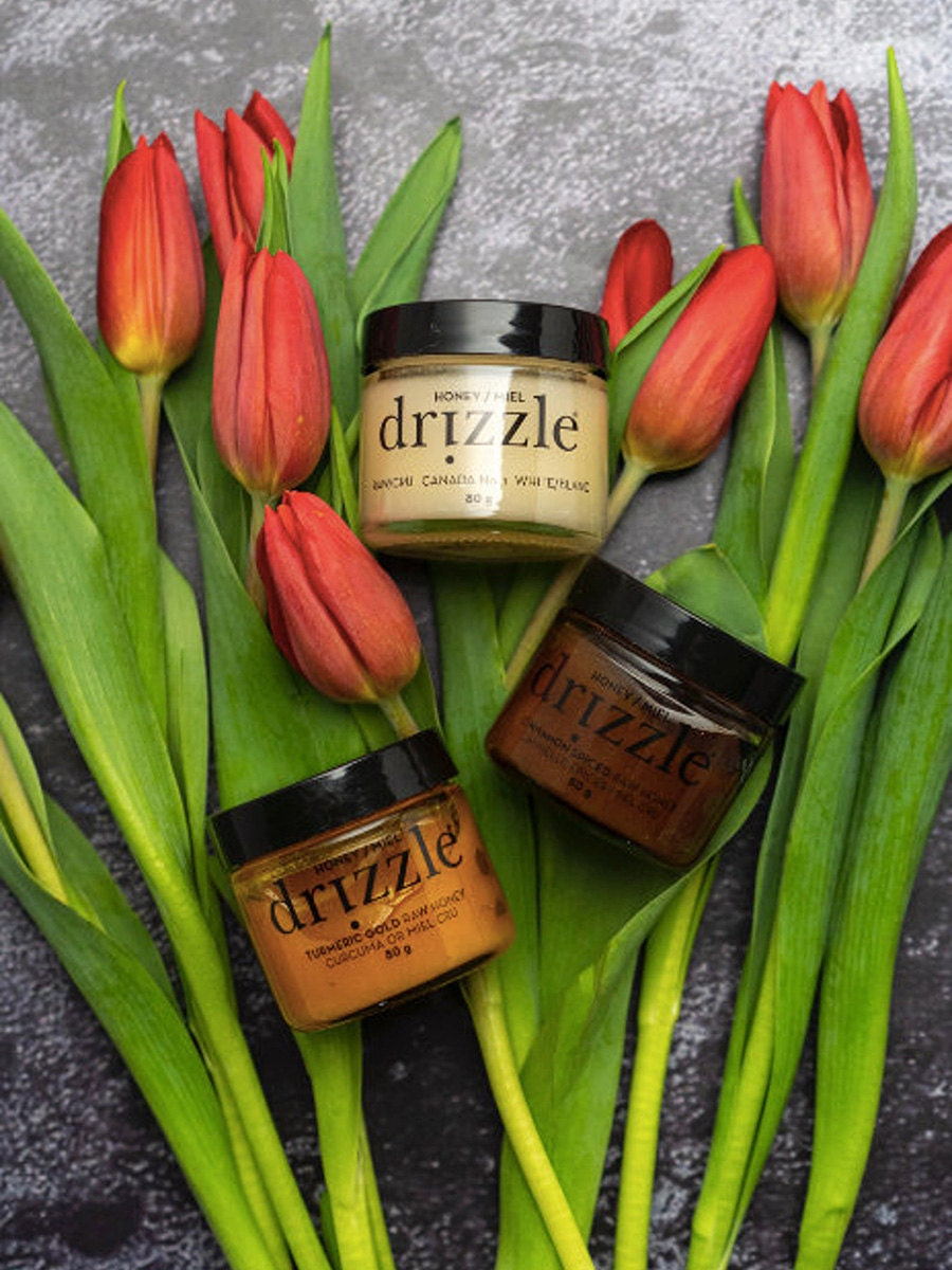 Three jars of honey against a stone backdrop with tulips.