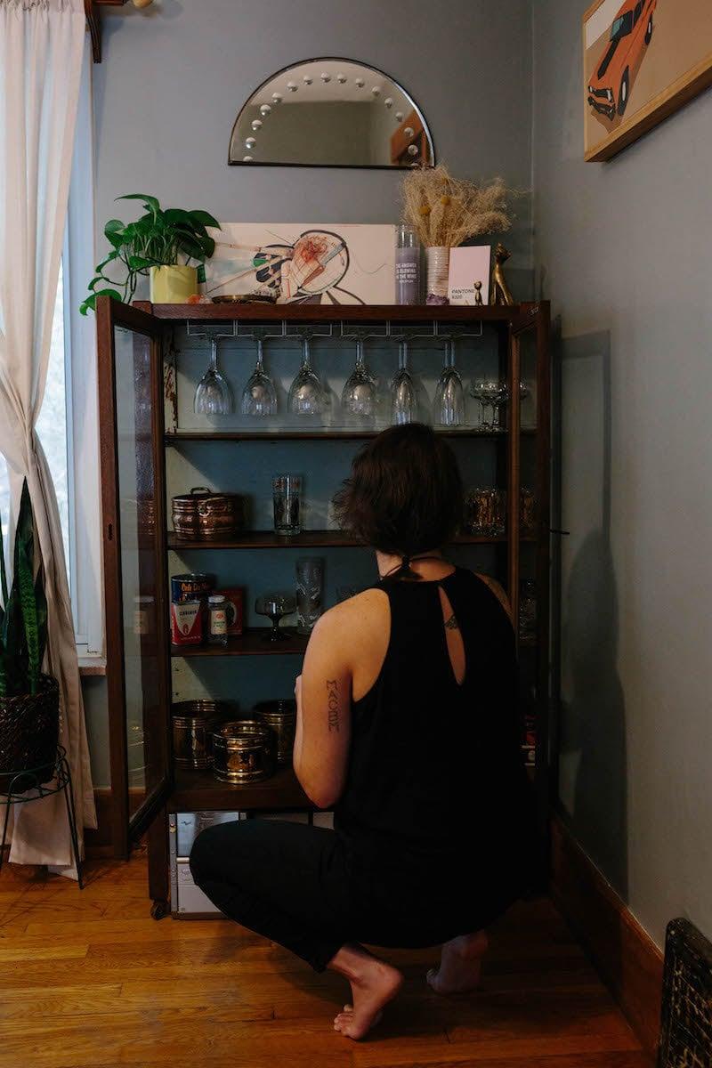 Brenda arranging glassware on a shelf in her home