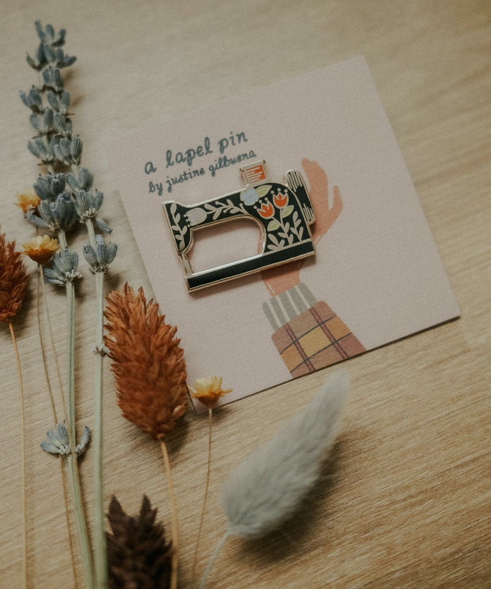 A sewing machine enamel pin from Justine Gilbuena