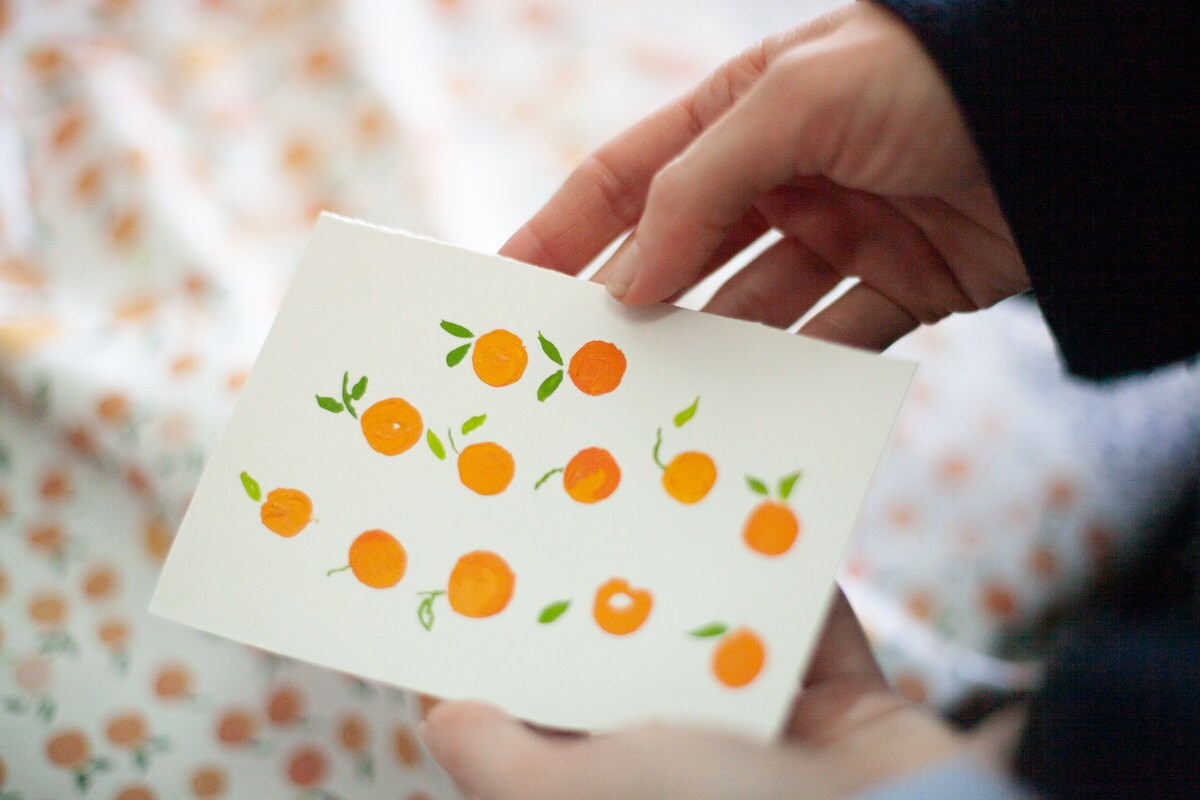 Hadas holds a piece of paper painted with her orange pattern