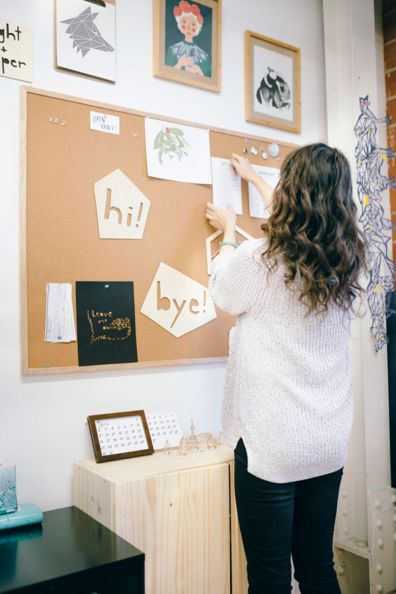 Ali hanging up notes on her bulletin board in her studio.