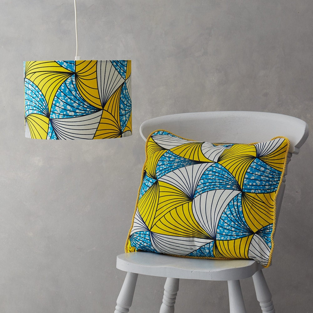 A matching blue and yellow African wax print lampshade and pillow cover from Bespoke Binny,