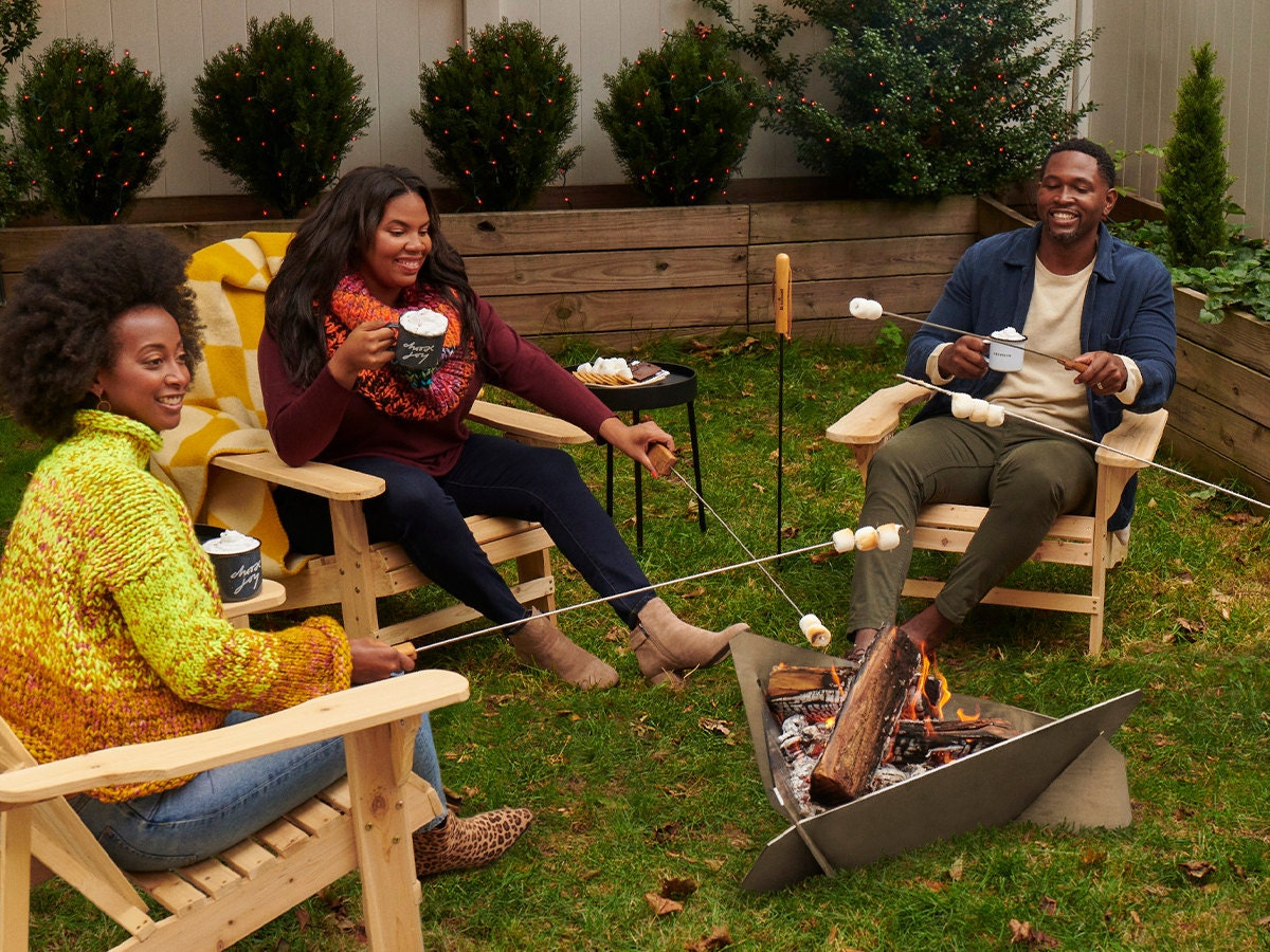 Three people sit around an outdoor firepit