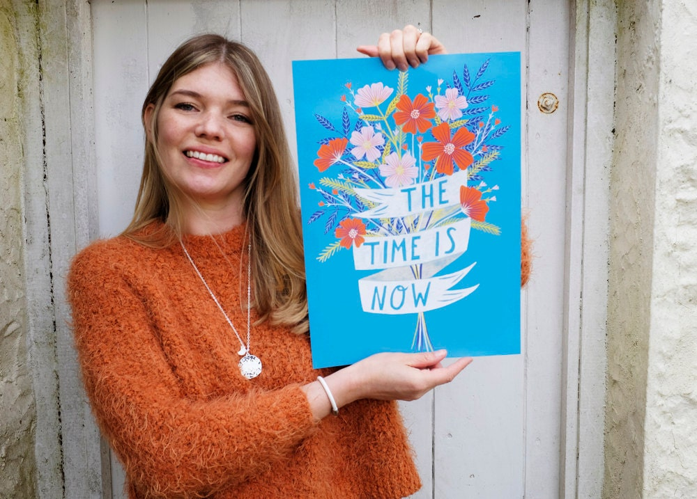 Lee holds up one of her colorful floral prints.