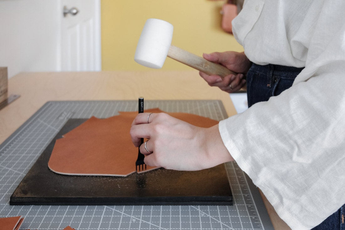 Quynh uses a mallet to make holes in a piece of leather