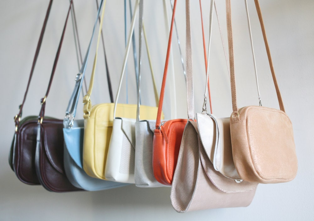 A rainbow-colored assortment of handbags from Alex Bender hanging from a rack