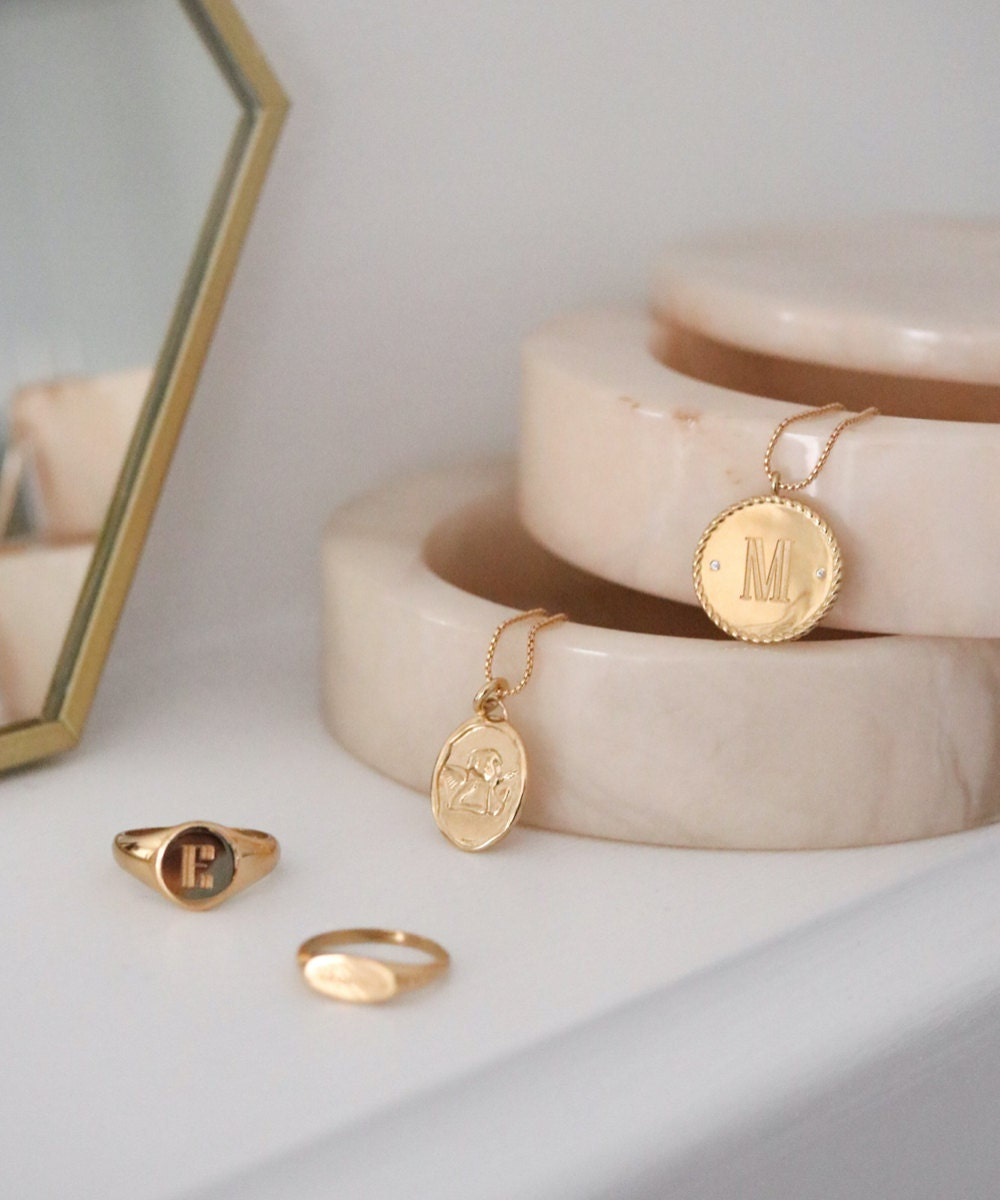 Assorted engraved, personalized gold signet rings and necklace pendants from EVREN, displayed in a marble jewelry box.