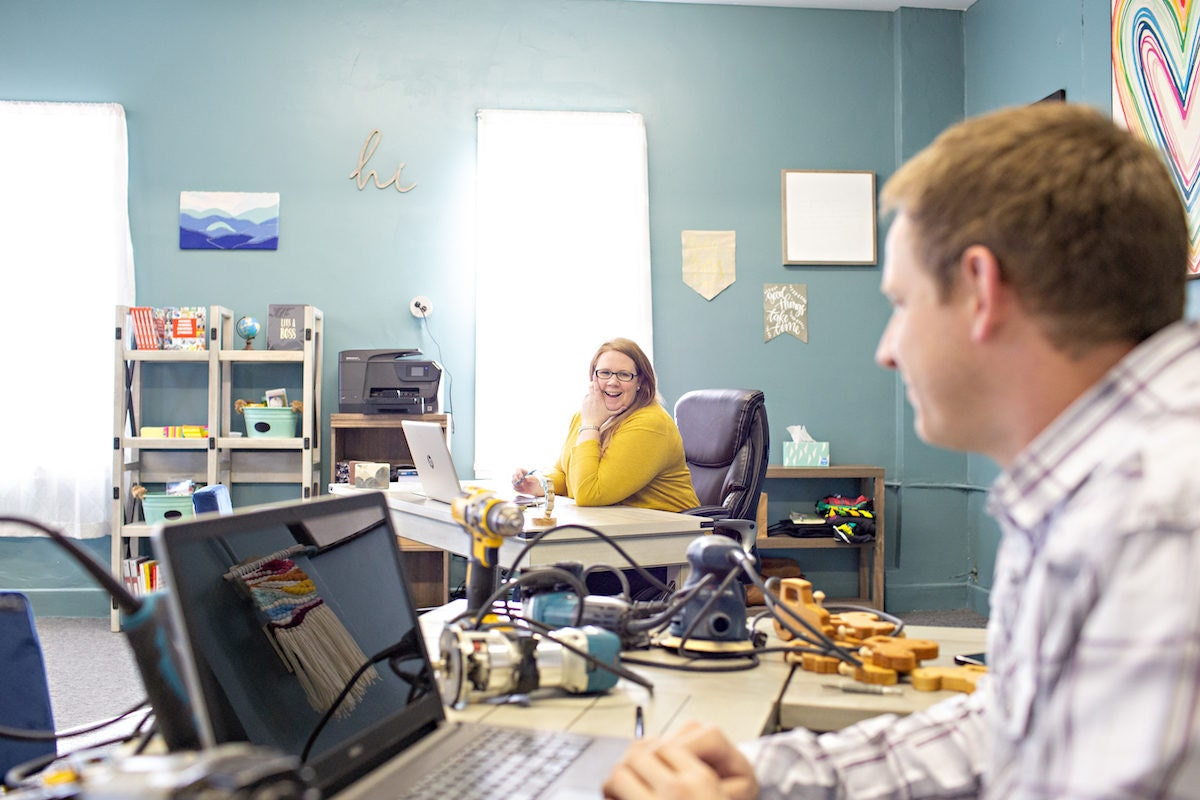 Stacey and Jesse Bannor chatting at their desks in the Bannor Toys office