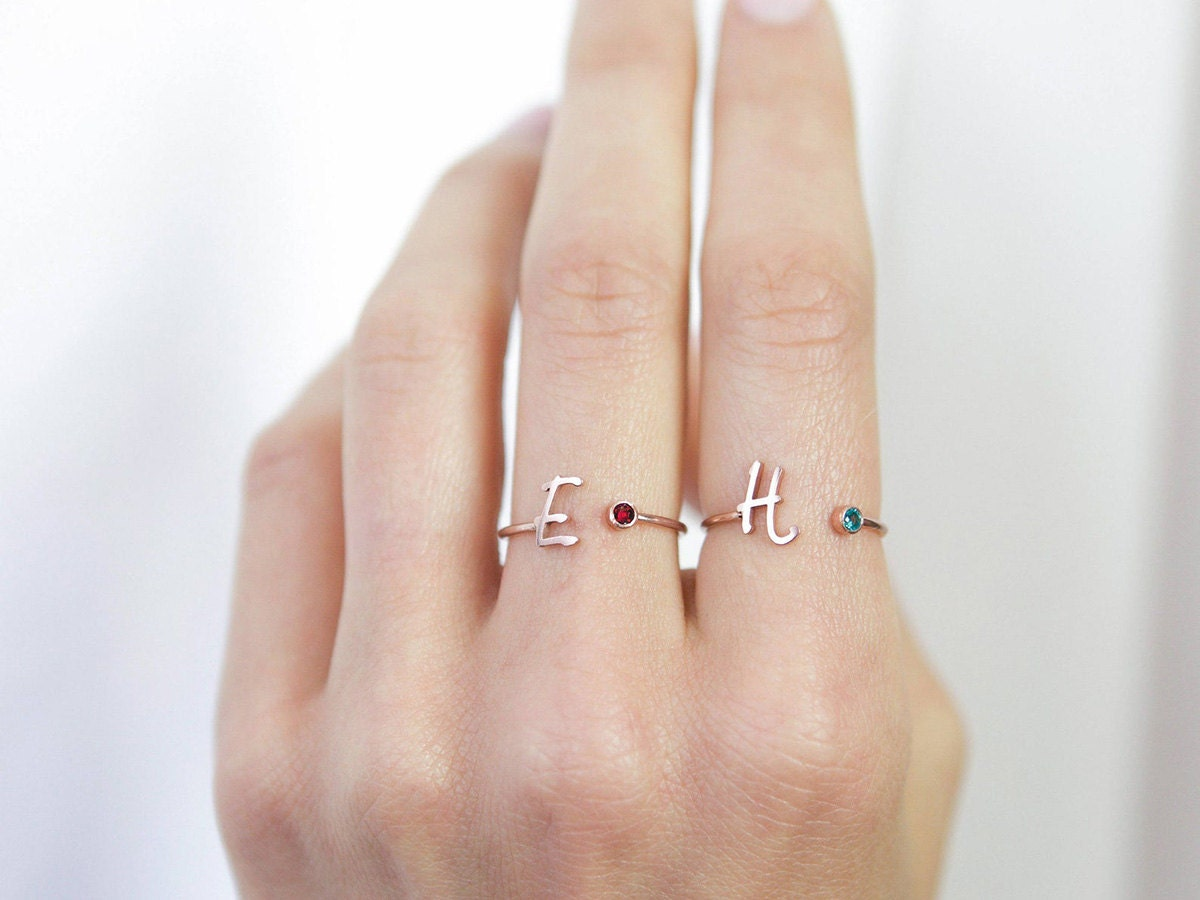Two initial and birthstone rings on a model.