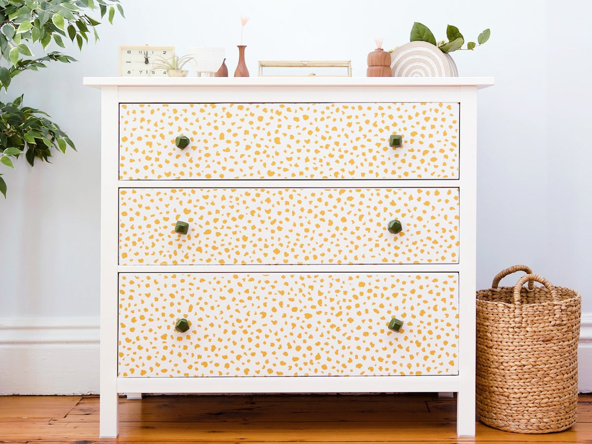 A dresser decorated with peel-and-stick yellow speckled wall paper.