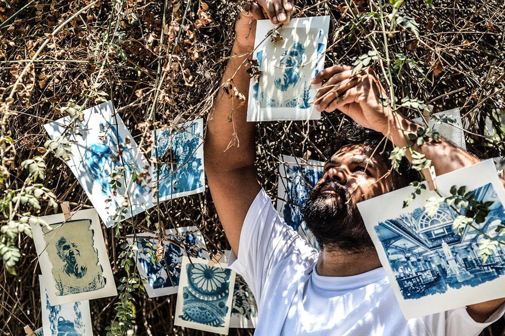 A person hanging up cyanotype prints in the sun