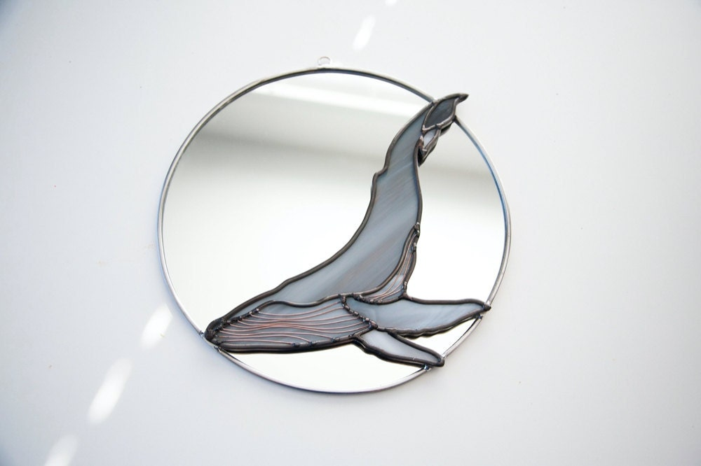 A circle mirror decorated with a stained glass humpback whale from Szklo Glass
