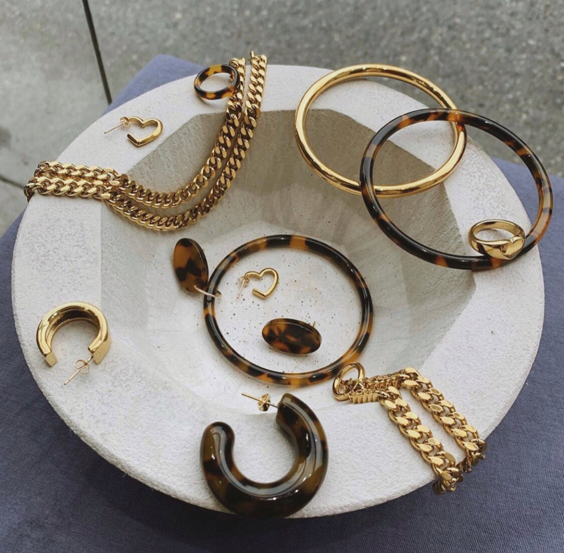 Assorted pieces from the Foe & Dear ready-to-wear collection displayed in a dish.