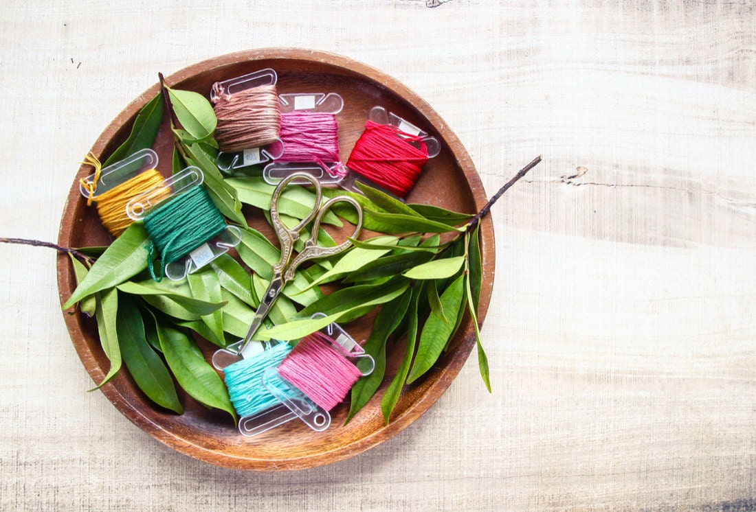 A wooden bowl full of colorful embroidery floss and a pair of embroidery scissors