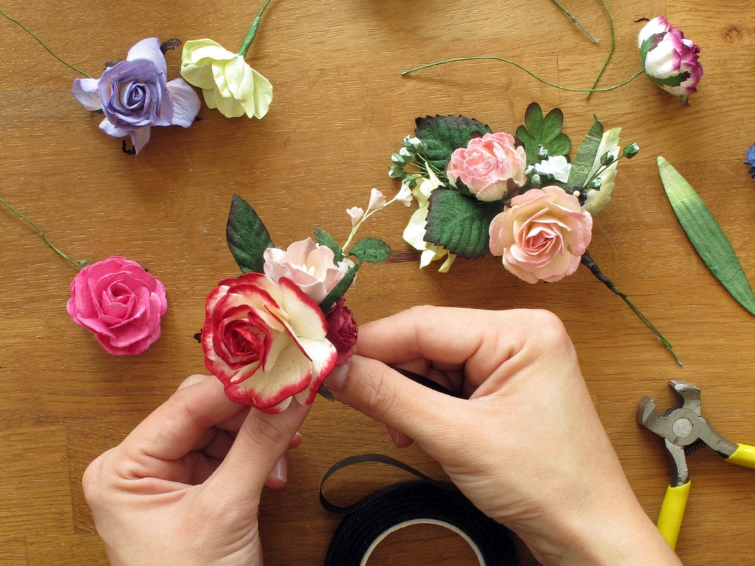 Orawee assembles colorful paper flowers into a harmonious batch for crafting