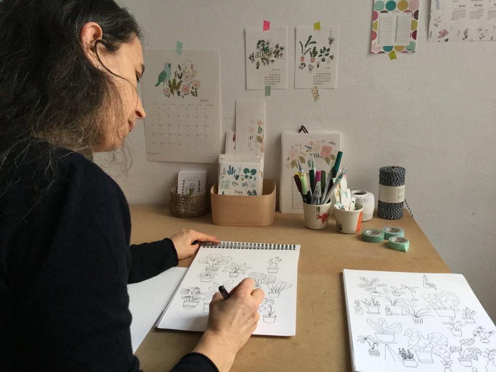 Yolande Six drawing in her sketchbook at her desk