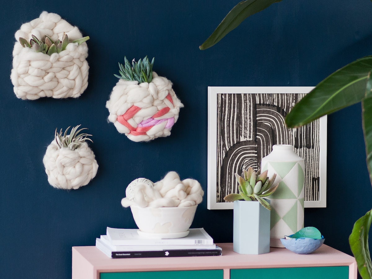 DIY woven wall pockets filled with plants, hanging above a desk