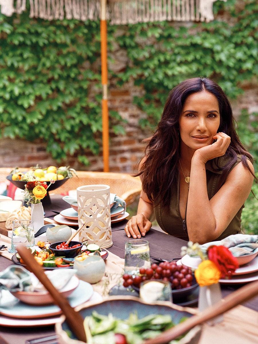 Padma Lakshmi sits at a table outside