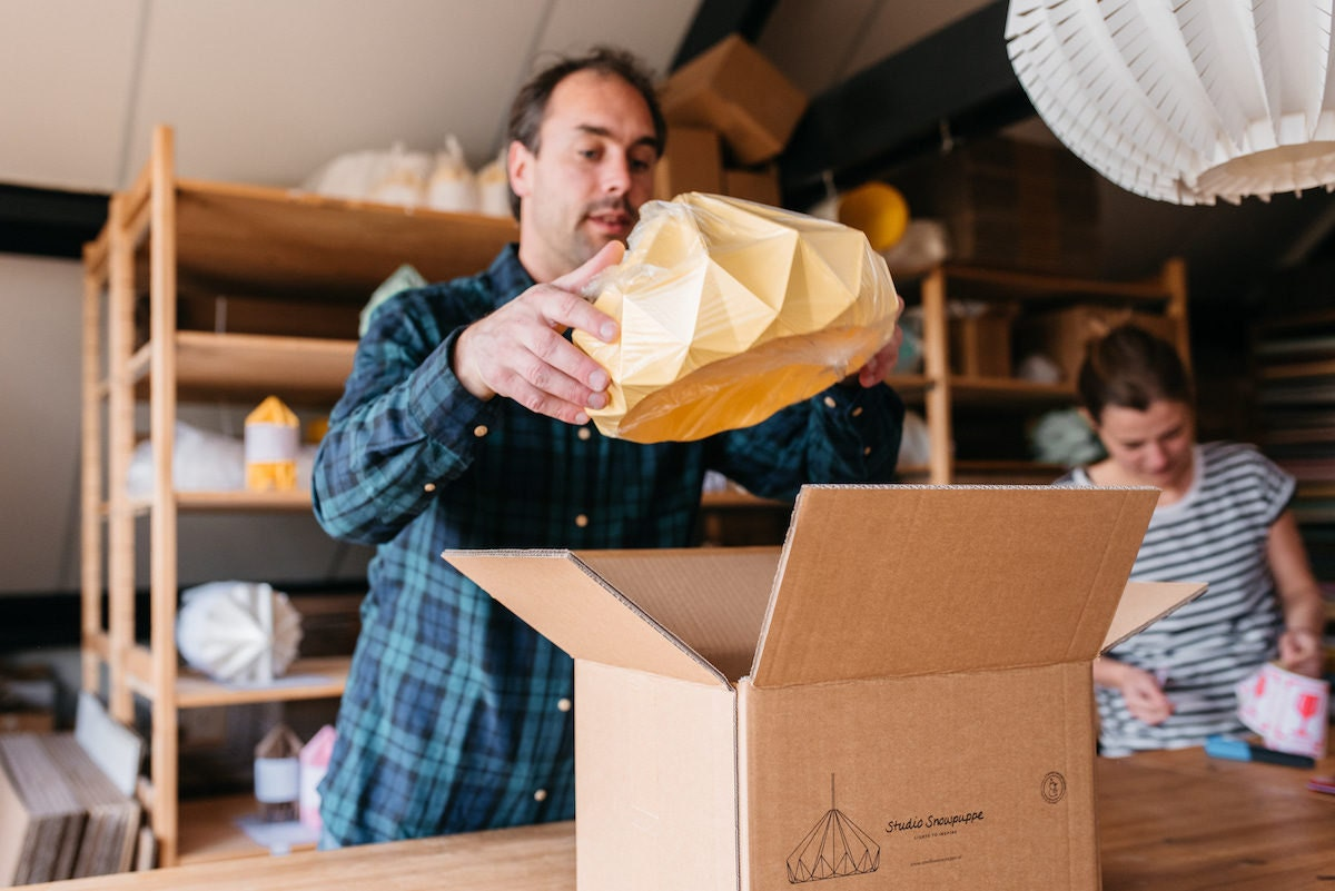 Kenneth places a finished yellow lampshade into a cardboard box for shipping