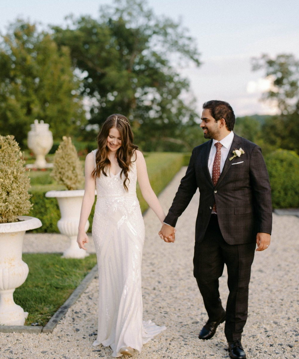 A portrait of Megan Oppenheimer and Imran Hoosain holding hands on their wedding day.