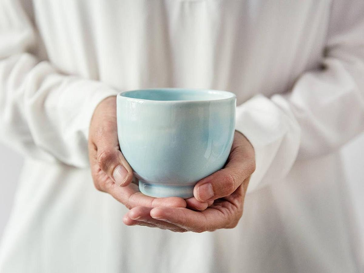 Closeup of a woman holding a blue teacup from Odaka in the palms of her hands.