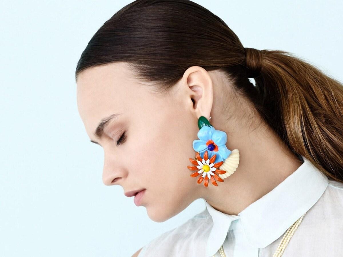 Enamel flower earrings on a model.