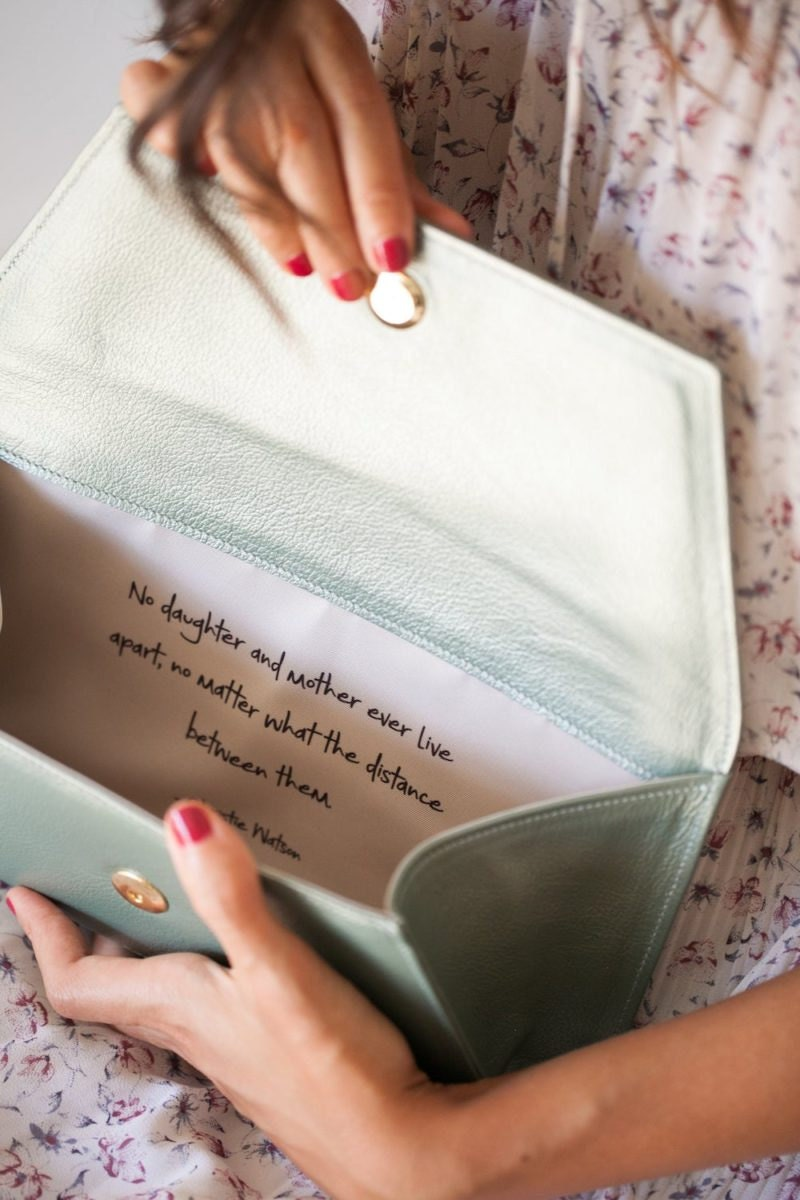 A woman holds open a personalized clutch from Fontém to see the note inside.